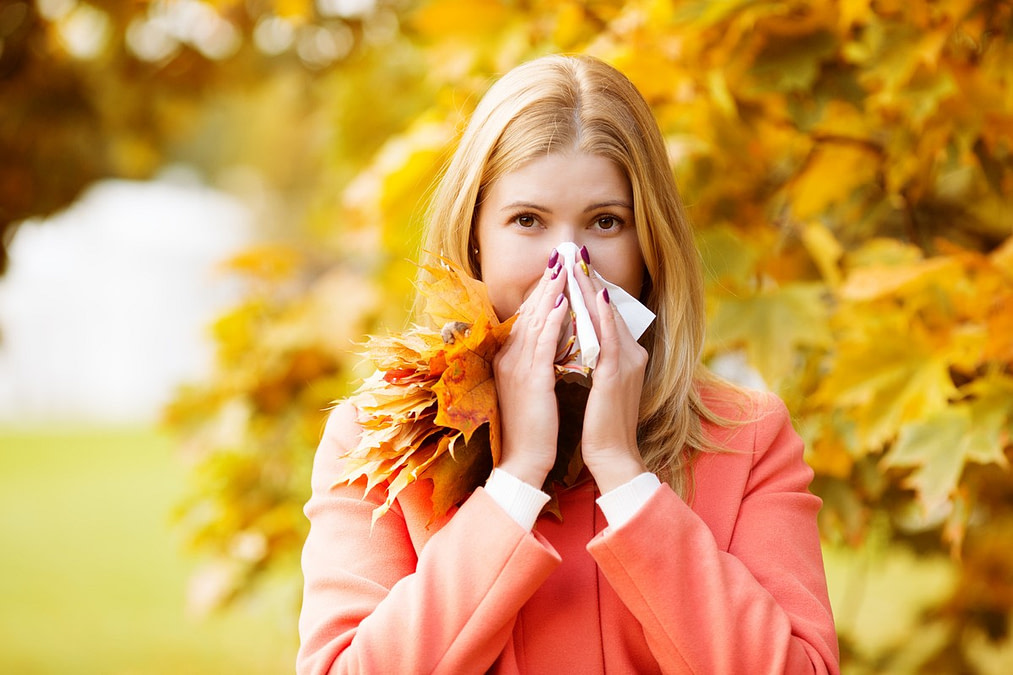 Girl with cold rhinitis on autumn background. Fall flu season. Ill sick sneezing woman. Handkerchief, vaccine against influenza virus Caught Cold Headache Allergy runny nose